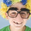 Young boy wearing clown wig and fake nose smiling — Stock Photo