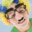 Young boy wearing clown wig and fake nose - Stock Photo