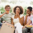 Royalty-Free Stock Photo: Group Of Teenagers Sitting On A Couch Eating Pizza