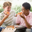 Teenage Boys Sitting On Couch Eating Pizza Together — Stock Photo #4782193