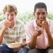 Teenage Boys Sitting On Couch Eating crisps Together — Stock Photo #4782194