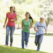Foto Stock: Teenagers Running Through Park