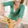 Teenage Girl Making Peanut Butter Sandwich - Stock Photo