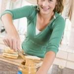 tonårig flicka att göra jordnötssmör smörgås — Stockfoto