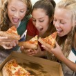 Teenage Girls Eating Pizza - Stock Photo