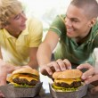 图库照片: Teenage Boys Eating Burgers