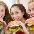 Teenage Girls Eating Burgers - 图库照片