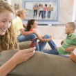 Teenagers Hanging Out In Front Of Television Using Mobile Phones — Stock Photo #4782343