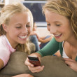 Teenagers Hanging Out In Front Of Television Using Mobile Phones — Stock Photo #4782351