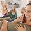 Stock Photo: Teenagers Hanging Out In Front Of Television Using Mobile Phones