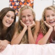Teenage Girls Lying On Bed Using Mobile Phone — Stock Photo