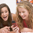 Teenage Girls Lying On Bed Using Mobile Phone — Stock Photo #4782376