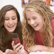 Teenage Girls Lying On Bed Using Mobile Phone — Stock Photo #4782377