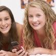 Stock Photo: Teenage Girls Lying On Bed Using Mobile Phone