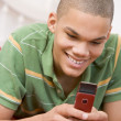 Stock Photo: Teenage Boy Lying On Bed Using Mobile Phone