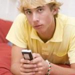 Teenage Boy Lying On Bed Using Mobile Phone — Stock Photo #4782425