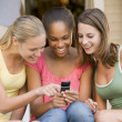 Teenage Girls Sitting Outside Playing With Mobile Phone - Photo