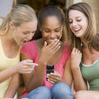 Stock Photo: Teenage Girls Sitting Outside Playing With Mobile Phone