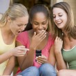 Teenage Girls Sitting Outside Playing With Mobile Phone - Stock Photo