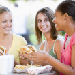 Stock Photo: Teenage Girls Sitting Outdoors Eating Fast Food