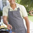 Man Barbequing In A Garden - Stock Photo