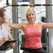 Personal Trainer Watching Woman Weight Train - Stock Photo