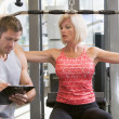 Stock Photo: Personal Trainer Watching WomWeight Train