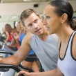 Personal Trainer Encouraging Woman Using Treadmill At Gym — Stock Photo #4785382