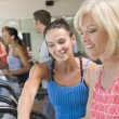 Personal Trainer Showing Woman How To Use Treadmill - Stock Photo