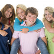 Teenage Girls Piggy Back On Boys - Stock Photo