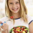Stock Photo: Young Girl Eating Fresh Fruit Salad
