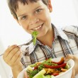 Foto Stock: Young Boy Eating Healthy Salad