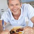Middle Aged Man Eating Unhealthy Fried Breakfast - Stock Photo