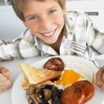 giovane ragazzo mangiando colazione fritta malsana — Foto Stock
