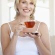 Mid Adult Woman Holding Tea Cup And Smiling At Camera — Stock Photo #4787456