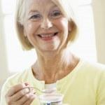 Senior Woman Eating Yogurt — Stock Photo
