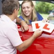 Teenage Girl Receiving Her Learner Plates - Stockfoto