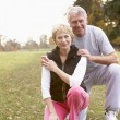 Stock Photo: Portrait Of Senior Couple Crouching In Park