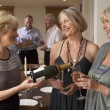 Woman Serving Champagne To Her Guests At A Dinner Party — Stock Photo