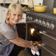 Woman Taking Food Out Of The Oven — Stock Photo #4789042