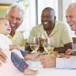 Stock Photo: MShowing His Baby Granddaughter To Friends At Restaurant