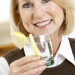 Woman Having A Drink At Home — Stockfoto
