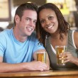Couple Drinking Beer Together In A Pub - Stock Photo
