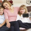 Mother And Children On Sofa Being Filmed On Video Camera - Stock Photo