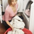 Unhappy Woman Doing Laundry - Stockfoto