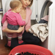 Woman Doing Laundry And Holding Baby Daughter - Stockfoto