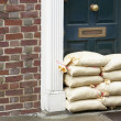 Sandbags Stacked In A Doorway In Preparation For Flooding - Stock Photo
