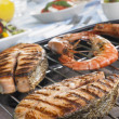 Salmon And Prawns Cooking On A Grill - Stock Photo