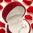 Foto de Stock  : Diamond Ring In Heart Shaped Box Surrounded By Rose Petals