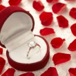Diamond Ring In Heart Shaped Box Surrounded By Rose Petals - Стоковая фотография